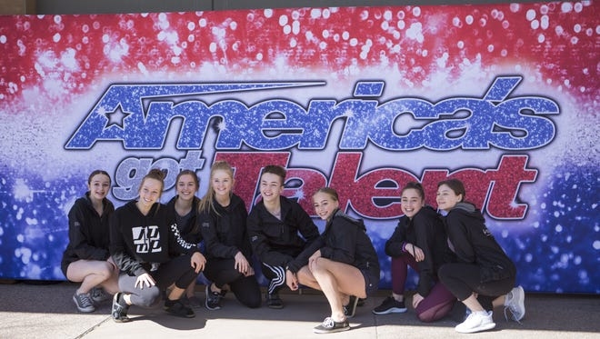 Contestants pose with the 'America's Got Talent' sign outside the Phoenix auditions being held at the Phoenix Convention Center on Saturday, Feb. 24, 2018.