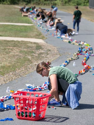 Students, teachers & parents work to assemble the worlds largest LEGO chain at the Clark Mill's Elementary school in Manalapan. Fran Bloom, a parent, works on the chain—September 13, 2016-Manalapan, NJ.-Staff photographer/Bob Bielk/Asbury Park Press