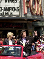 Marian and Mike Ilitch rode an open car  in the Red