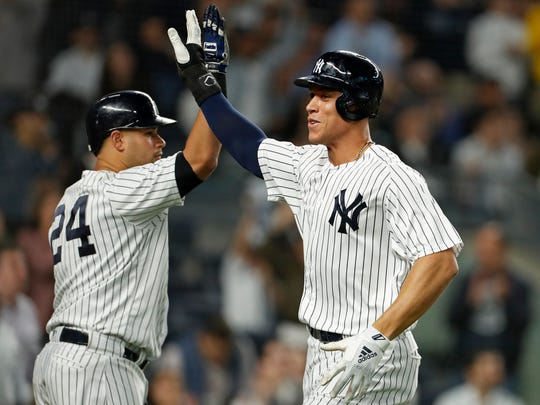 New York Yankees right fielder Aaron Judge (99) celebrates scoring a run with New York Yankees catcher Gary Sanchez against the Boston Red Sox during the third inning at Yankee Stadium.