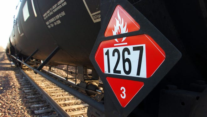 FILE - This Nov. 6, 2013 file photo shows a warning placard on a tank car carrying crude oil near a loading terminal in Trenton, N.D. North Dakota Public Service Commissioner Julie Fedorchak wants the state to employ its own railroad safety inspectors to help monitor crude shipments coming from the oil patch. Fedorchak says the idea is aimed at preventing accidents like the fiery oil train crash outside Casselton in December that left an ominous cloud over the town and led some residents to evacuate. (AP Photo/Matthew Brown, File)