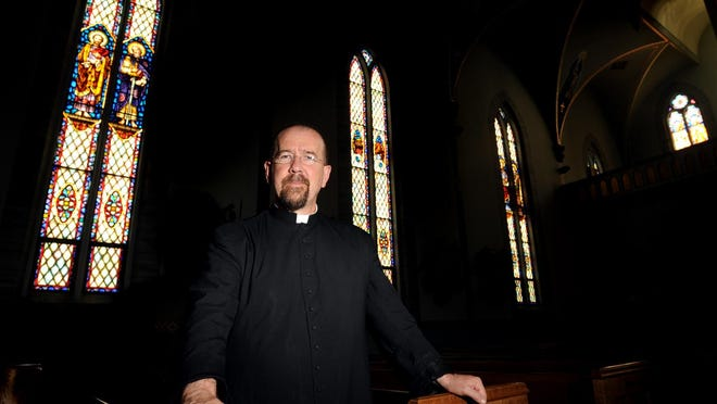 The Rev. Stephen Rooney is pictured at St. Michael Catholic Church in Monroe in 2008.