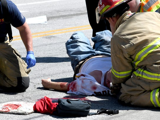 Firefighters and paramedics treat a man after he suffered