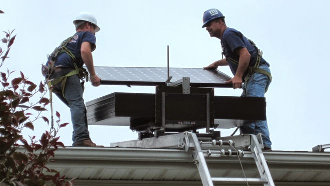 ETM crew members Steve Mihok (left) and Ken Franklyn (right) install a solar panel.