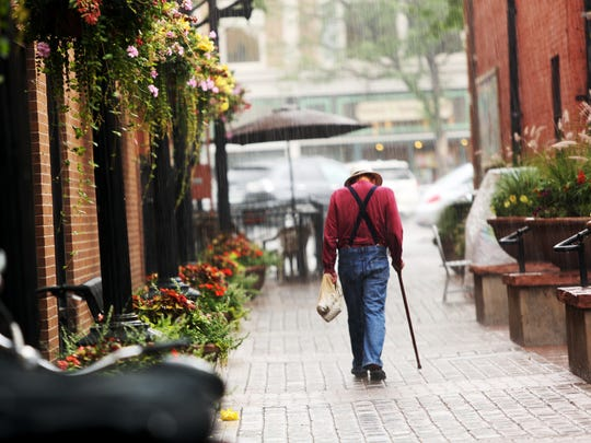 A man walks through the rain at Trimble Court in Old Town Friday, July 18, 2014.