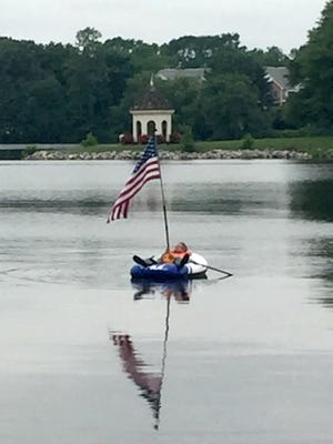 Donald Sauter looks up at the American flag from his rubber dingy Monday on Silver Lake. The Dover man said he has floated for a few hours each Memorial Day and Fourth of July the past three or four years to show his patriotism.