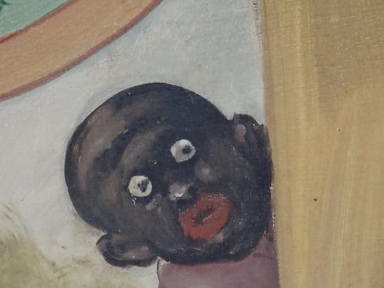 A close-up of a painted panel at the Ontario Beach Park carousel that features two caricatures of African-Americans.