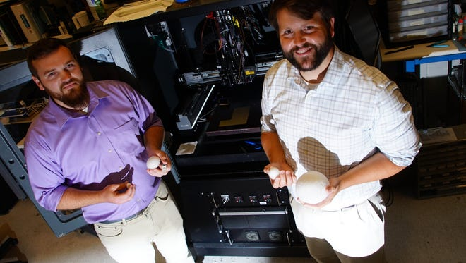 Zachary Larimore (left) and Paul Parsons are the co-founders of a Newark startup that is pushing the boundaries of what 3-D printing can do in the fields of telecommunications, defense contracting and pharmaceuticals. The duo are holding radar antennas of various sizes they made using the 3-D printer behind them.