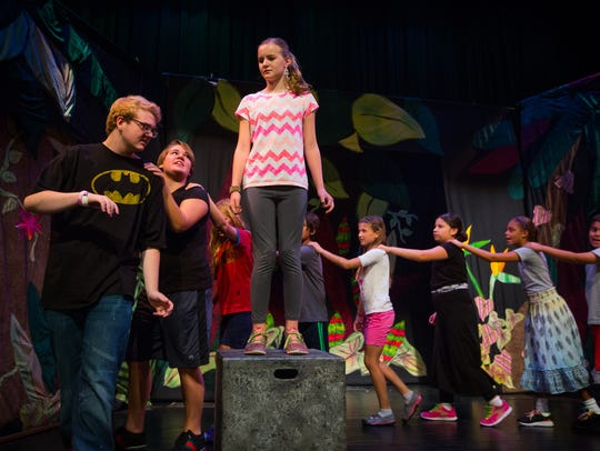 12-year-old Brynn Olsen, center, playing the part of