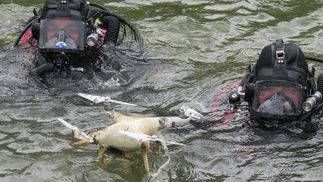 Divers Mark Peltier and Jared Daniel recover a drone from the Black River Saturday.