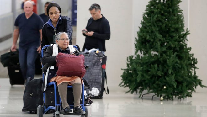 An employee pushes a woman on a wheelchair out of the international arrivals area at Newark Liberty International Airport on Nov. 21, 2017, in Newark, N.J.