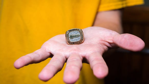 Nathan St. Onge, quarterback and wide receiver for the AC Reynolds football team, holds his brother Justin's state championship ring in the weight room at his family's home Wednesday, December 6, 2017. Reynolds will compete with New Hanover for the state title this Saturday in Durham.