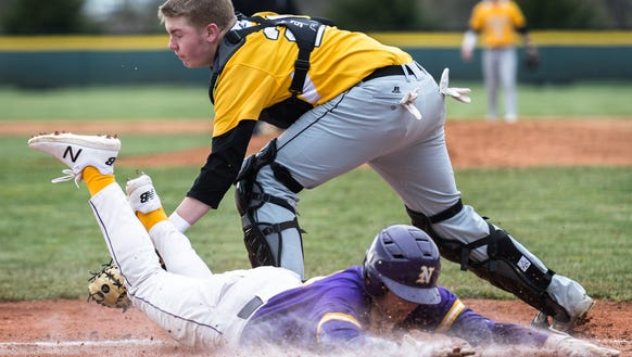 North Henderson's Nate Toney slides safely into home plate avoiding the tag of Tuscola's Patrick Broom during their game Friday, March 9, 2018. North Henderson defeated Tuscola 5-2 in 11 innings.