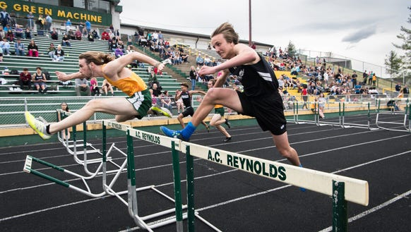 Boys compete in the 100 meter hurdles event at the