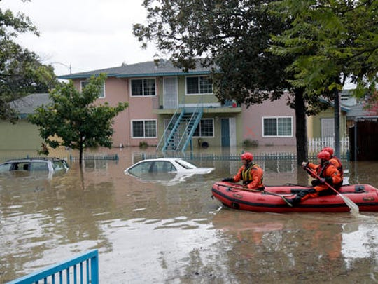 Rescuers travel by boat through a flooded neighborhood looking for stranded residents Tuesday, Feb. 21, 2017, in San Jose, Calif. Rescuers chest-deep in water steered boats carrying dozens of people, some with babies and pets, from a San Jose neighborhood inundated by water from an overflowing creek Tuesday.
