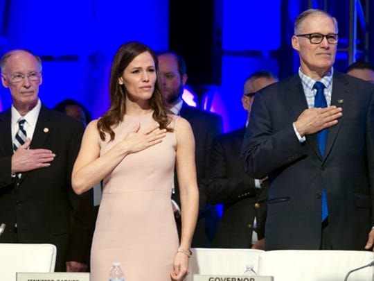 Actress Jennifer Garner, center, Alabama Gov. Robert Bentley, left, and National Governors Association (NGA) Vice Chairman Jay Inslee stand for the Posting of the Colors during the NGA's Winter Meeting in Washington, Saturday, Feb. 25, 2017.