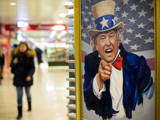 People walk past a caricature picture of U.S. President Donald Trump on sale in a shopping mall in Moscow, Russia, Wednesday, March 22, 2017. President Donald Trump's former campaign chairman, Paul Manafort, secretly worked for a Russian billionaire to advance the interests of Russian President Vladimir Putin a decade ago and proposed an ambitious political strategy to undermine anti-Russian opposition across former Soviet republics, The Associated Press has learned.