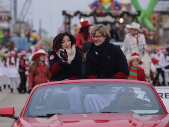 Olympic Gold medalists Meryl Davis and Charlie White wave to the crowd while riding along Woodward Avenue  in downtown Detroit on Nov.  27, 2014, as the 2014 America's Thanksgiving Parade grand marshals.