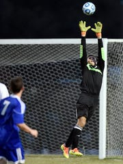 Memorial goal keeper Max Durchholz leaps high for the save while facing Bloomington South during the second half of the Boys 2A regional at at Jasper High School Thursday.  Memorial won on penalty kicks to advance.