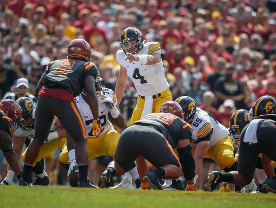 Iowa quarterback Nate Stanley tries to pull the Iowa