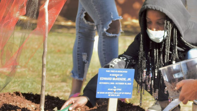 "North Aiken Elementary School fourth-grader Ja'Kaila Lee pours dirt on a new tree in the school's courtyard Monday in memory of her late big brother Edward ""Junior"" F. McKenzie Jr."