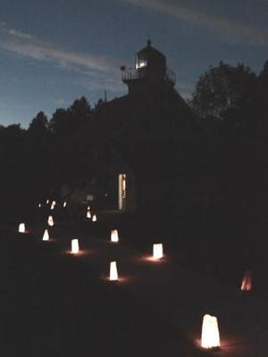 """Luminarias light the path to Eagle Bluff Lighthouse and its shining Fresnel lens for last year's """"Twilight Tours, Tunes & Tales."""""""