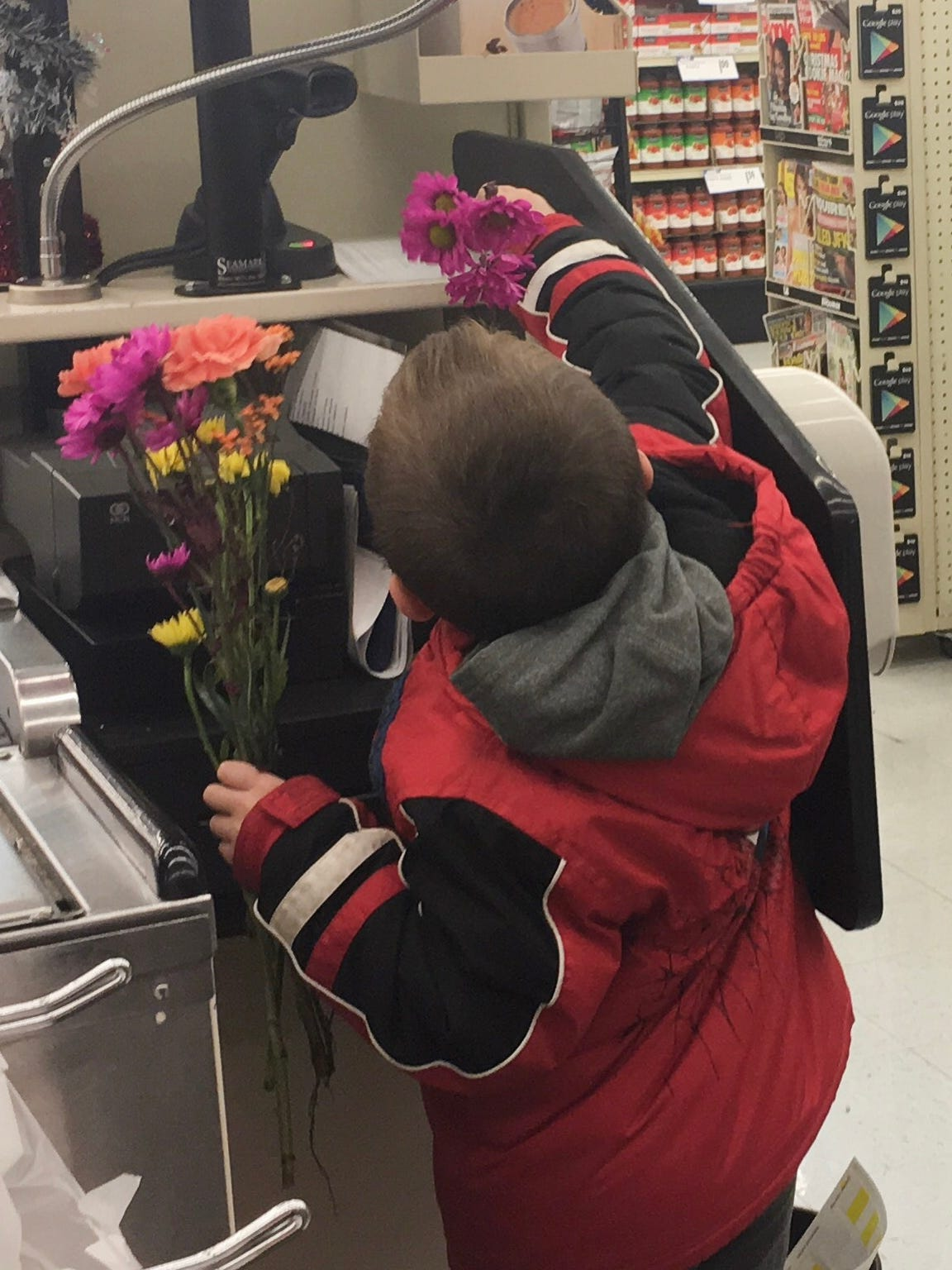 Connor Brindle, 6, puts a flower on a cash register