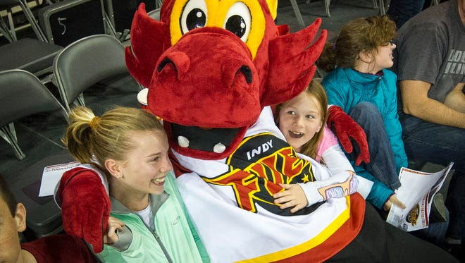 Indy Fuel mascot, Nitro, makes space for himself on top of two young fans, Sarah Coates, 12, left, and Mackenzie Hiatt, 8, both of Westfield, during the third period of action. ECHL hockey team, The Indy Fuel, played Evansville Icemen, Sunday, October 12, 2014, at the recently renovated Fairgrounds Coliseum at the Indiana State Fairgrounds. The team, Indianapolis' newest professional sports team, was the first sporting event at the facility after it re-opened this summer.