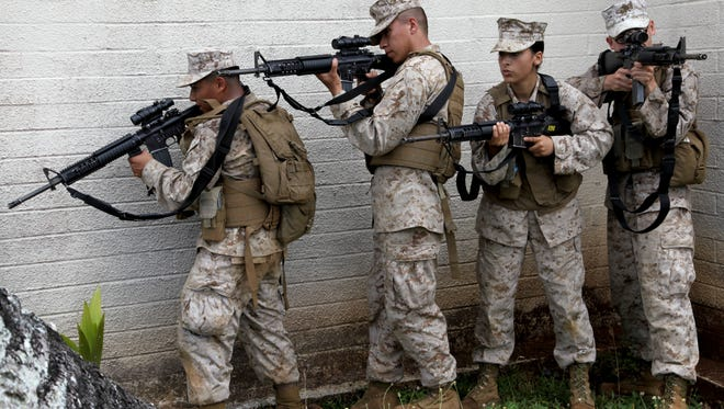 In this April 2013 file photo, Lance Cpl. Mary C. Dalessandro and her squad stack and prepare to enter an abandoned housing unit during Military Operations in Urban Terrain training April 25 while on a field operation during Exercise Guahan Shield.