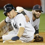 Boston Red Sox second baseman Dustin Pedroia, right, looks from behind New York Yankees Brett Gardner after putting Gardner out when New York Yankees designated hitter Alex Rodriguez hit into a fifth-inning double play Tuesday.