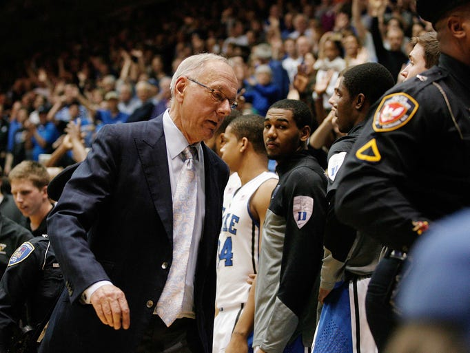 Syracuse coach Jim Boeheim is escorted off the court after being ejected from a game against the Duke Blue Devils at Cameron Indoor Stadium.