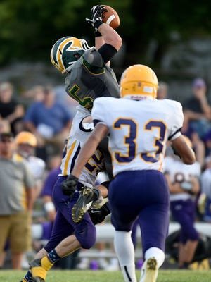 Northeastern's Connor Bray catches the ball as Hagerstown's David Castle catches him Friday, Sept. 9, 2016, during a football game in Fountain City.