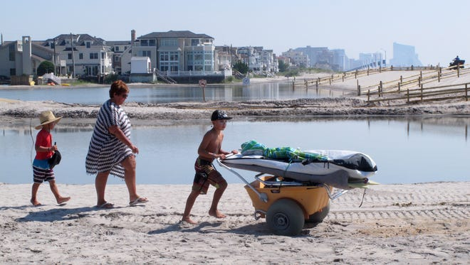 Beachgoers cross over one of numerous large pools of water that have formed on the beach in Margate due to heavy rains.