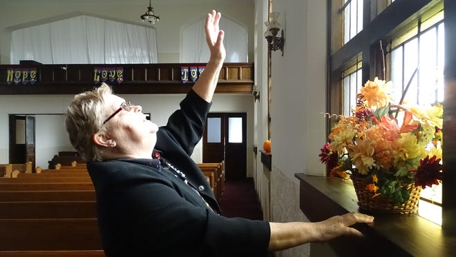 Pastor Gale Green, of First United Church of Christ in Marion, points out some of the details in the stained glass windows, which the church is trying to salvage before the building is torn down.