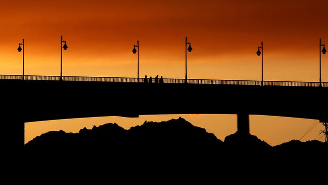Pedestrians cross the Manette Bridge at sunset on Saturday, May 5, 2018.