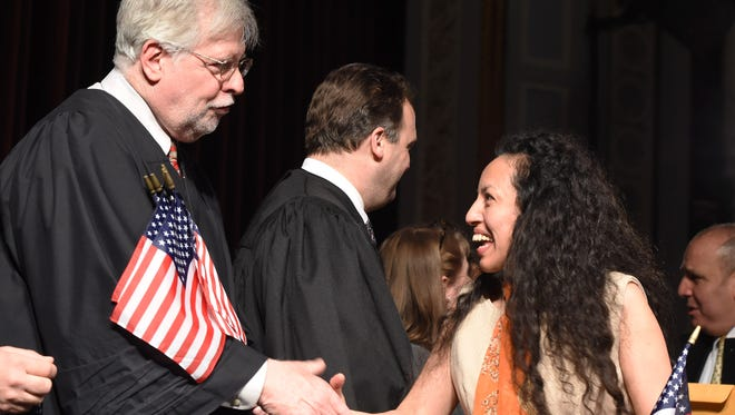 Marcial Ortiz, right, a Mexican immigrant from Hyde Park, shakes hands with Dutchess County Court Judge Peter Forman, left, at a naturalization ceremony at the Bardavon 1869 Opera House in the City of Poughkeepsie.
