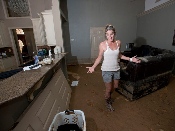 Homeowners Stephanie Oberhausen searches her home for anything of value, days after the family home was flooded out in the Woodbridge subdivision. The Oberhausenâ??s home was destroyed after a storm water retention behind their home burst during last weekâ??s heavy rains and flooding.