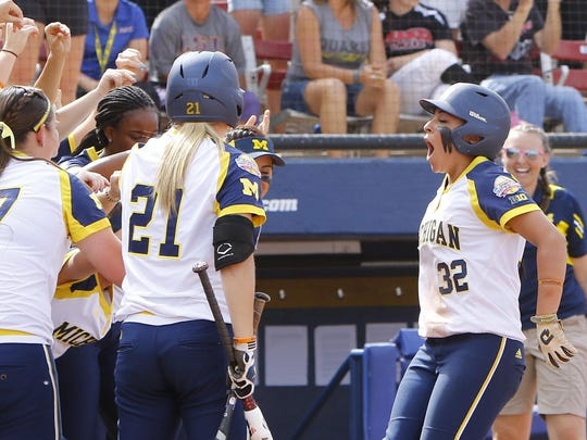 Michigan's Sierra Romero is greeted at home plate after scoring against LSU at the Women's College World Series in Oklahoma City last season.