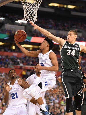 Duke guard Quinn Cook  lays the ball up past Michigan State Spartans forward Gavin Schilling in the second half of the 2015 NCAA Men's Division I Championship semi-final game at Lucas Oil Stadium.
