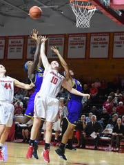 Marist College's Maura Fitzpatrick jumps for a rebound against two Delaware defenders on Thursday at McCann Arena.