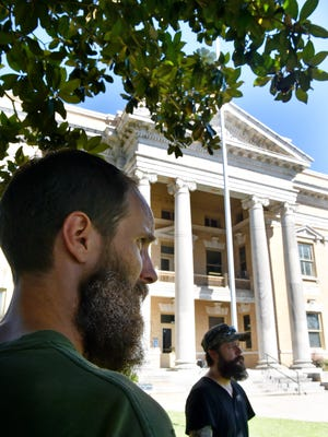 """Jones County resident Joseph Hosey, left, and Paul Johnson stand in the shade of a magnolia tree outside the Ellisville courthouse. Hosey and Johnson are extras in the film """"Free State of Jones,"""" set in Civil War-era Jones County."""