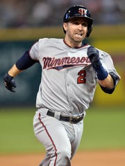 Minnesota Twins second baseman Brian Dozier (2) runs into third base with a triple during the eighth inning Wednesday against the Cleveland Indians at Progressive Field in Cleveland, Ohio.