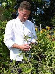 Thomas Kacherski, head chef and owner of Crew Restaurant & Bar in the Town of Poughkeepsie, takes a look at some produce growing in the garden behind the restaurant.