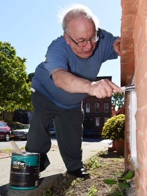 Jeffrey Hughes, 72, of the City of Poughkeepsie paints the window frames of his house.