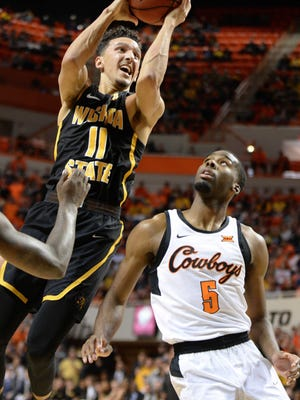 Wichita State Shockers guard Landry Shamet (11) shoots the ball over Oklahoma State Cowboys guard Tavarius Shine (5) during the first half at Gallagher-Iba Arena.