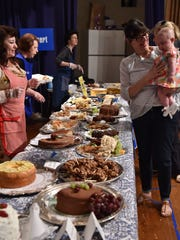 Ann Blackwell, second from right, and granddaughter Emma Evans visit the dessert table at last year's Beth Israel Bazaar.