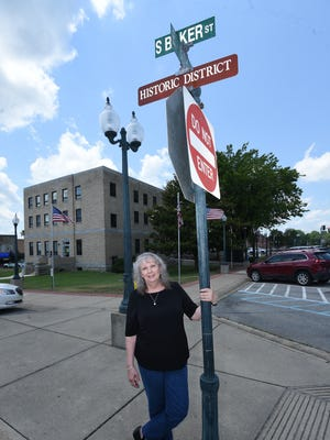 Maryanne Edge stands below one of 19 streets signs designating The Mountain Home Commercial Historic District. Edge was instrumental in getting the signs placed around the district.