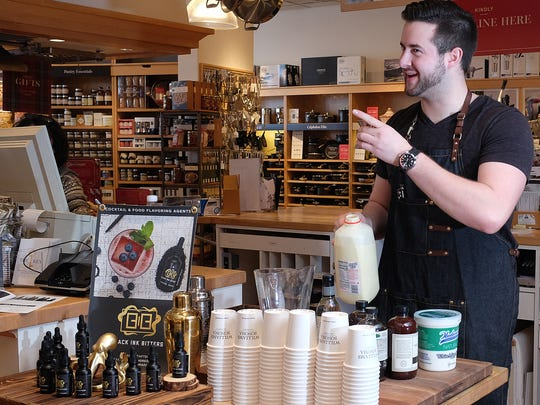 Mike Fair jokes with a customer at Williams-Sonoma as he prepares a tasting demonstration of his Christmas cocktails he makes with his brand of bitters Saturday, Dec. 9, 2017.