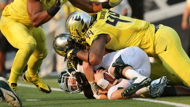 Michigan State's quarterback Conner Cook, bottom, ends up at the bottom of a pile of Oregon Ducks including Arik Armstead, left, Christian French and DeForest Buckner during the third quarter Saturday.