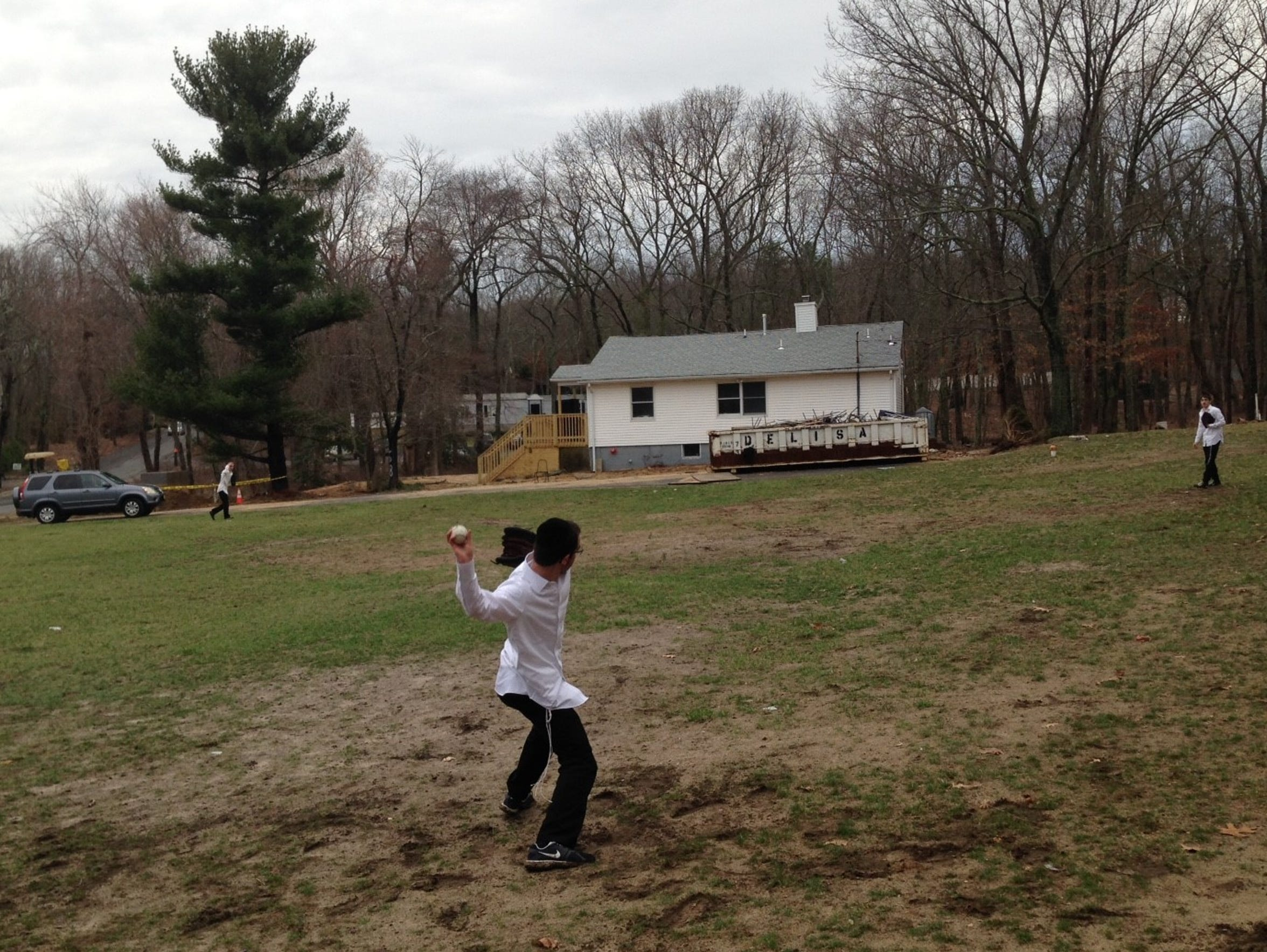 Three young yeshiva students play catch outside their